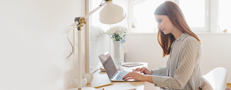 Młoda kobieta siedzące przy biurku i pracująca na laptopie